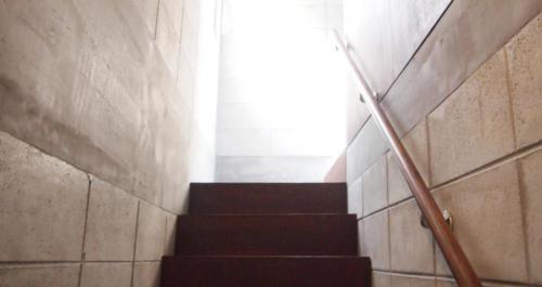 ダークブラウンの階段と無機質なコンクリートの壁が雰囲気を醸し出していますね。上がった先は何があるのでしょうか。