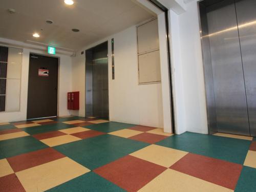 フロント横のエレベーターホールはカラフルなタイルが魅力的。